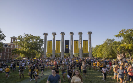 Mizzou students run through the Columns on MU's campus.