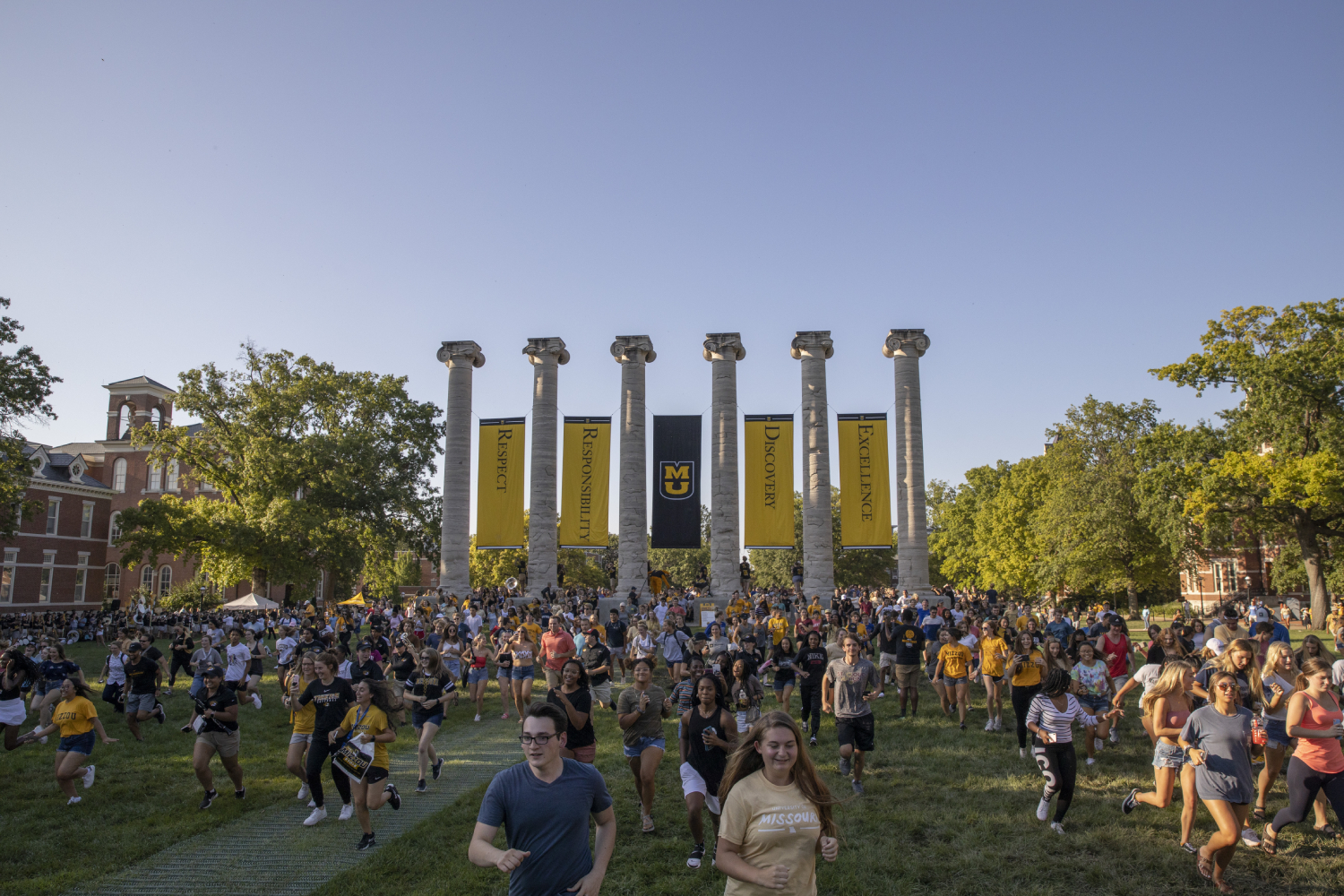 Mizzou students run through the Columns on MU's campus.