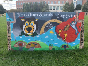 "A banner is emblazoned with the MU Homecoming 2019 theme ""Tradition Stands Forever."""