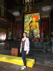 Rebecca Price in front of a Buddha statue at Mount Emei in Chengdu, Sichuan Province. July, 2018.
