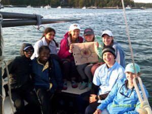 Molly McDermott and other students holding flag on sailboat