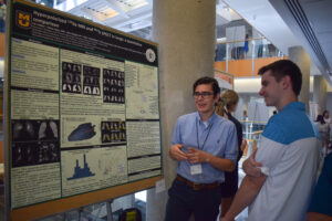 J.D. Peiffer explains his poster to a research forum attendant.