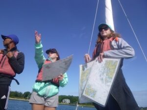 Molly McDermott holding the navigation charts on sailboat