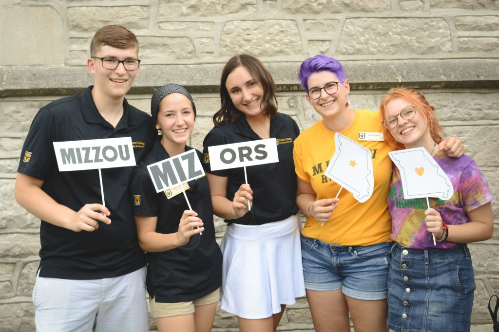 Students holding Mizzou Honors signs and smiling