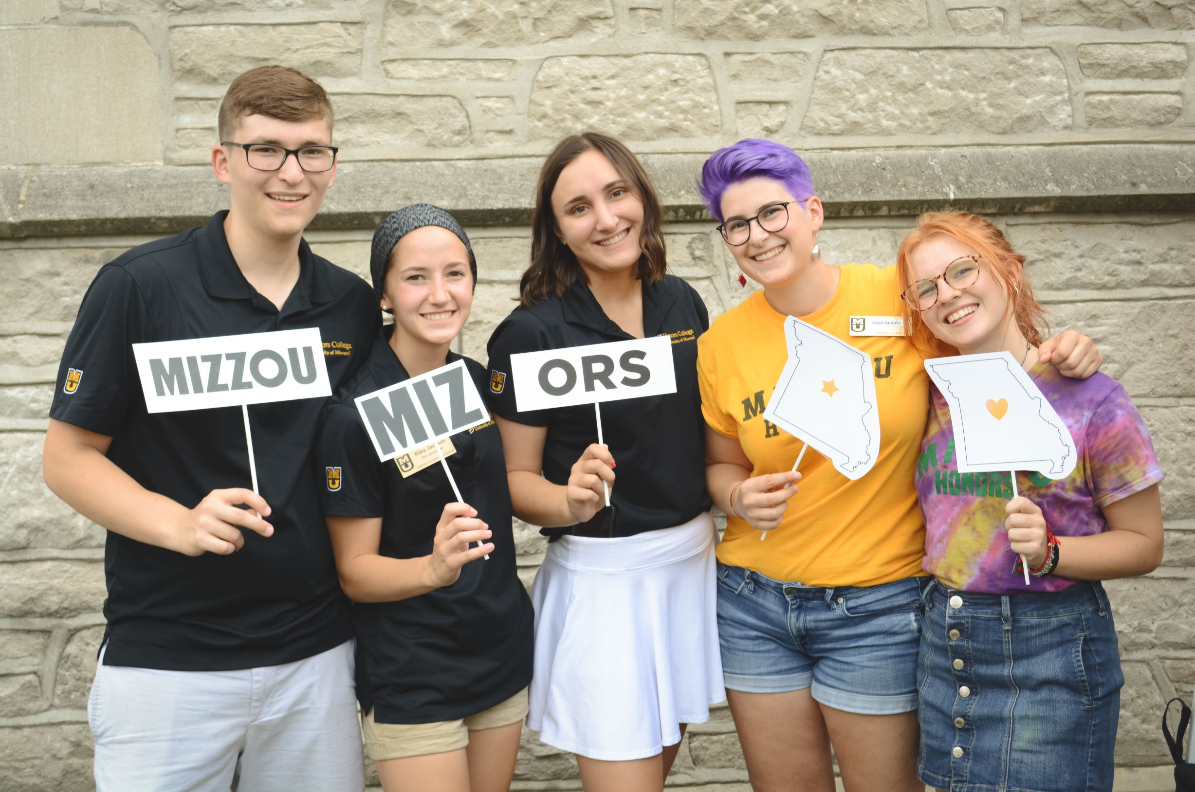 "Five Honors College students smiling and holding ""Mizzou"", ""MIZ"", and ""-ORS"" signs"