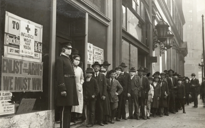 Historical photo of San Francisco residents lining up during the 1918 influenza pandemic.