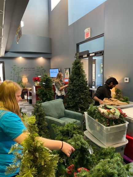 Scholars decorating with pine trees, boughs, and decorations